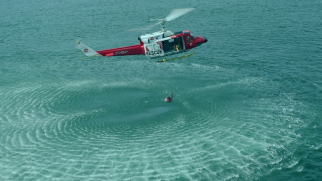 WS AERIAL ZI View of two men being airlifted out of sea / Cape Town, Western Cape, South Africa