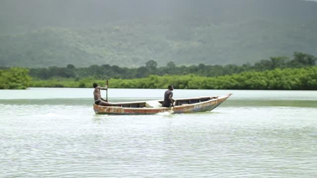 ws view of two men rowing in boat / freetown, sierra leone - sierra leone stock videos & royalty-free footage
