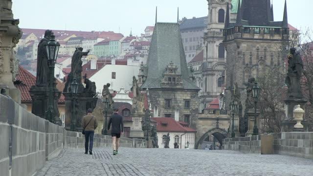 MS View of two men walking on charles bridge at early morning / Prague, Hlavni mesto Praha, Czech Republic