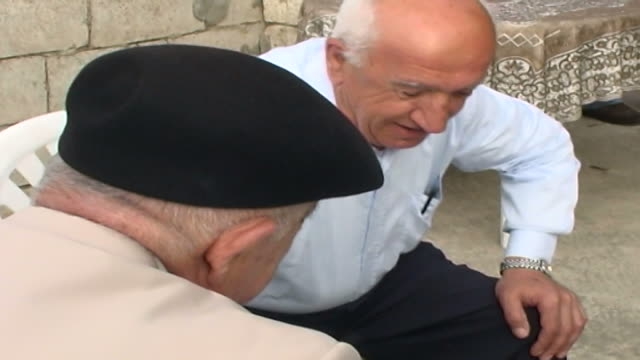 view of two old shia men playing dominoes on a veranda - sour taste stock videos & royalty-free footage