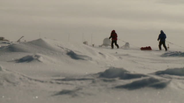 WS View of two people on skis pulling pack sleds across South Pole ice and Buildings / South Pole, Antarctica