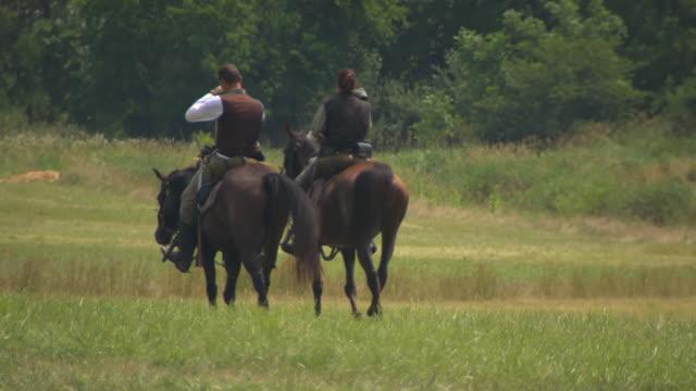 vídeos de stock e filmes b-roll de ws view of two soldiers on horseback ride their hats during battle of gettysburg / gettysburg, virginia, united states - gettysburg