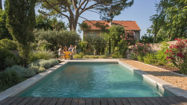 WS View of two women and two man having apero in beautiful garden and swimming pool / St. Remy de Provence, Provence, France
