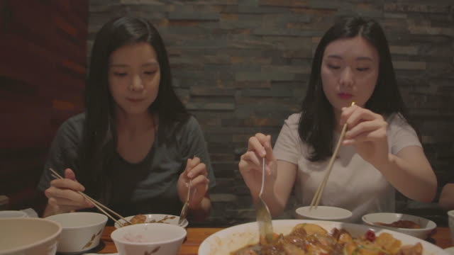 stockvideo's en b-roll-footage met view of two women eating some braised spicy chicken with vegetables (famous korean food) on a plate - koreaanse etniciteit
