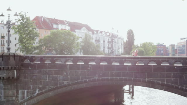 """""""ws view of two women walking across bridge, carrying picnic basket / berlin, germany"""" - picnic basket stock videos and b-roll footage"""