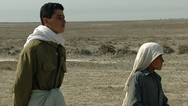 view of two young iraqi shepherds standing next to their flock of sheep. the sheep are grazing near a roadside in the desert. - 羊飼い点の映像素材/bロール