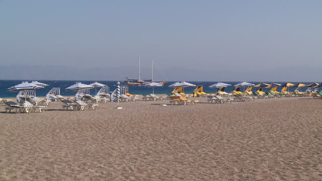 WS View of Umbrellas and Deckchairs in Wind Beach of west side Town / Rhodes, Dodecanese islands, Greece