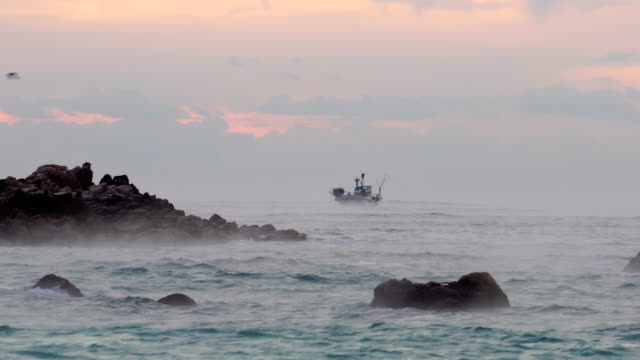 vidéos et rushes de view of underwater royal tomb of king munmu (30th ruler of the silla kingdom) (korea historic place 158) and fishing boat at sunrise - bateau de pêche
