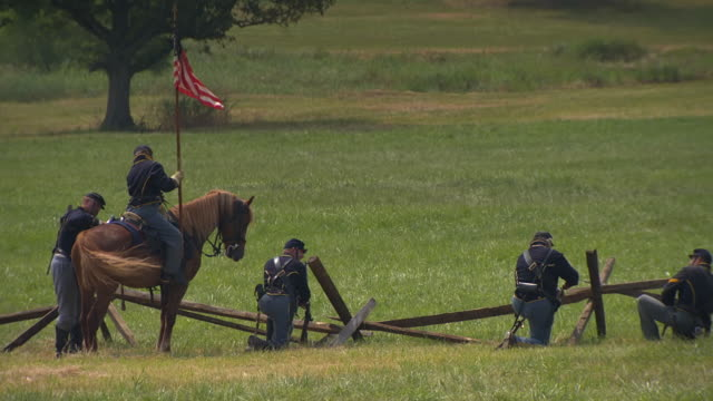 vídeos de stock e filmes b-roll de ws zo view of union soldier on horseback carries round pattern flag during battle of gettysburg / gettysburg, virginia, united states - exército da união
