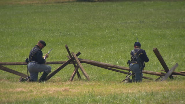 vídeos de stock e filmes b-roll de ws view of union soldiers kneeling behind wooden fence fire their rifles at same time during battle of gettysburg / gettysburg, virginia, united states - exército da união