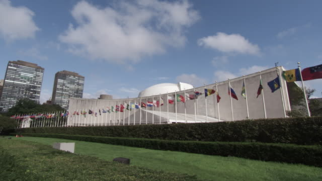 ws view of united nations flags flying above the others / new york, united states - united nations building stock videos and b-roll footage
