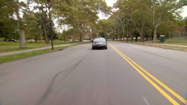 ws pov view of unmarked police car driving down street through park / pittsburgh, pennsylvania, united states  - polizeiauto stock-videos und b-roll-filmmaterial