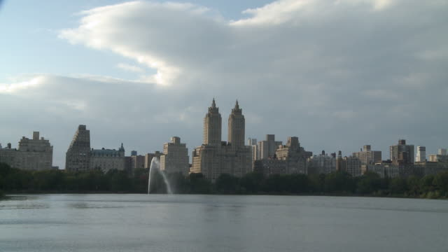 ws view of upper west side across jacqueline onassis reservoir in central park / new york, new york, united states - central park reservoir stock videos and b-roll footage