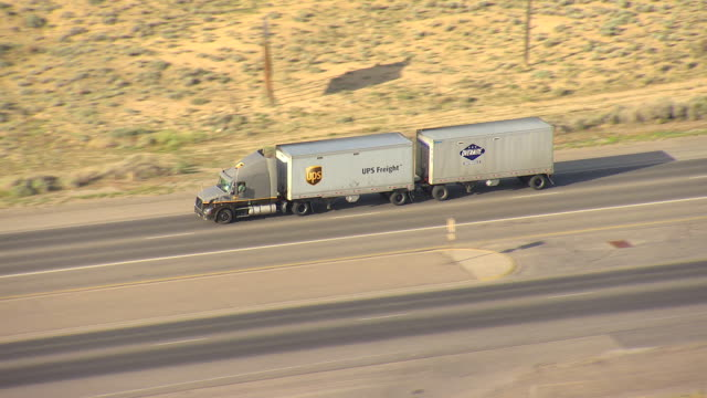 WS AERIAL TS View of UPS semi truck on highway in San Juan County / New Mexico, United States