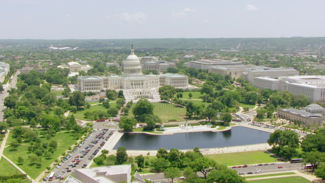 WS AERIAL POV View of US Capitol building with pool in foreground / Washington DC, United States