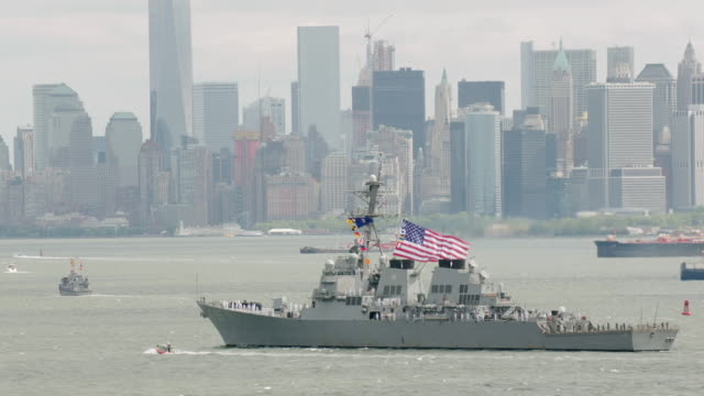 ms zo pov aerial view of us flag on navy ship and wtc in new york city / new york city  - military ship stock videos & royalty-free footage