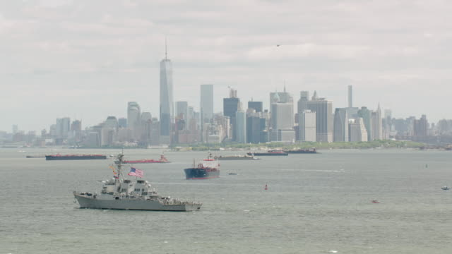 ms pov aerial view of us flag on navy ship and wtc in new york city / new york city  - military ship stock videos & royalty-free footage