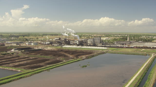 WS AERIAL View of US Sugar Corp Factory and smoke stacks blowing smoke into air in Hendry County / Florida, United States