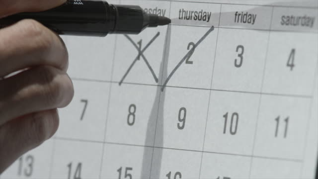 View of using black marker to cross out the line on a calendar