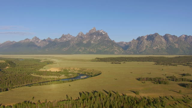 WS AERIAL View of Valley and Snake River to reveal Grand Tetons / Wyoming, United States