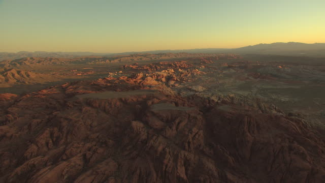 ws aerial view of valley of fire at dawn with sun peaking up / nevada, united states - nevada stock-videos und b-roll-filmmaterial
