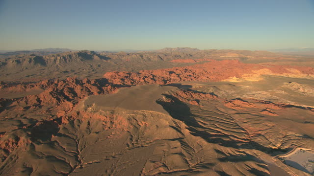 ws aerial view of valley of fire with red rock formations and light green ground cover in early morning / nevada, united states - nevada stock-videos und b-roll-filmmaterial
