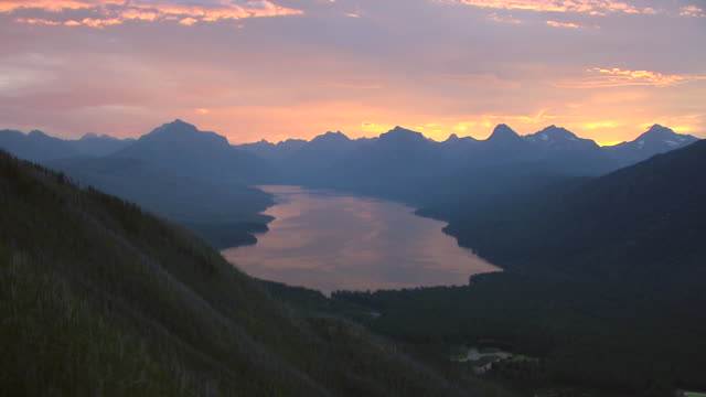 ws aerial view of valley with lake mcdonald at sunrise and mountains at glacier national park / montana, united states - montana stock-videos und b-roll-filmmaterial