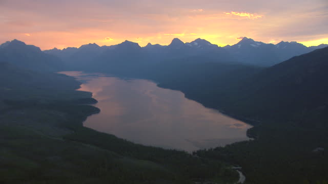 ws aerial view of valley with lake mcdonald at sunrise and mountains at glacier national park / montana, united states - 気まぐれな空点の映像素材/bロール