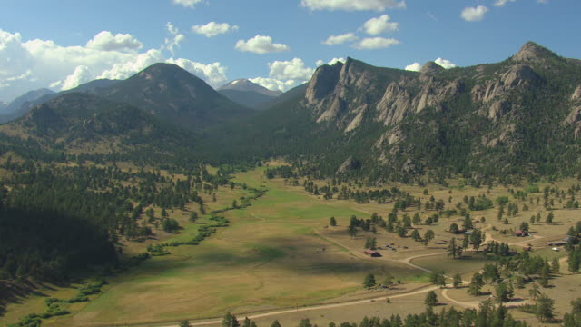 WS DS AERIAL View of valley with trees and rocky mountains with clouds and sunshine in sky / Estes Park, Colorado, United States