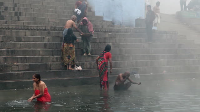 WS PAN View of Varanasi on River Ganges in Morning Fog people bathing / Varanasi, India
