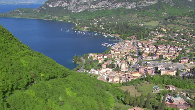 WS AERIAL View of various cities and villages around lake, boats and nature / Lake Garda, Trentino, Verona, Brescia