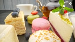 View of various sweets, including napoleon, cheesecake and other cakes, berries and teapot. Slider shot, 4K