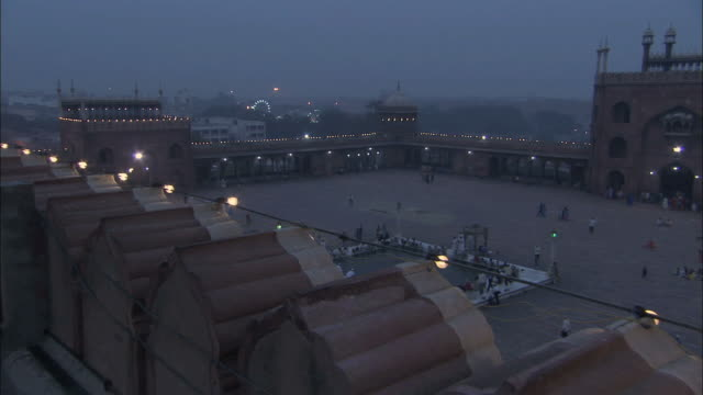 WS PAN View of vast courtyard of Jama Masjid mosque in Delhi, slowly filling with people for prayers at twilight