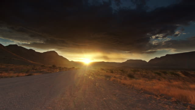 WS T/L View of Vehicle speeds by as sun goes down on craggy landscape leaving boiling fiery red apocolyptic clouds in dark sky / Damaraland, Windhoek, Namibia
