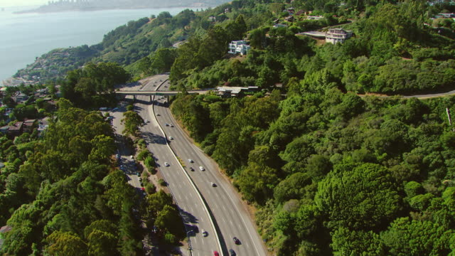 WS AERIAL View of vehicles running on highway surrounded by trees / Sausalito, California, United States