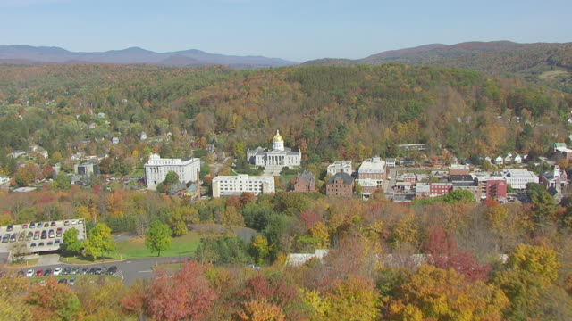 WS AERIAL POV View of Vermont State House with autumn forest area / Montpelier, Vermont, Unites States