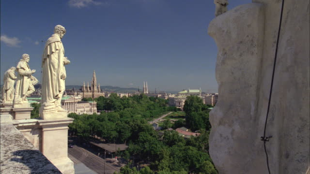 a view of vienna appears between the stone statues on a rooftop. - tornspira bildbanksvideor och videomaterial från bakom kulisserna
