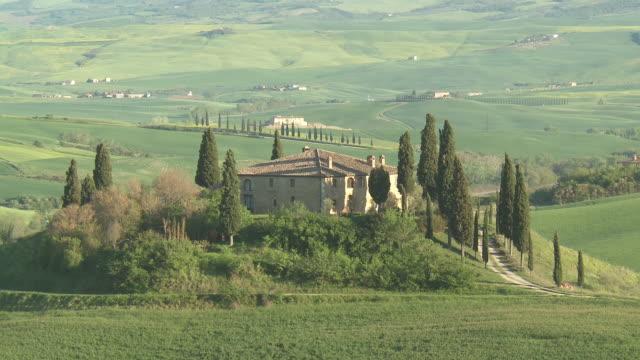 vidéos et rushes de ms view of villa belvedere farmhouse on hill at sunset / pienza, tuscany, italie - toscane
