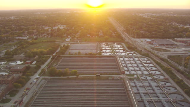 WS AERIAL POV View of village at sunset, vehicles moving on street / Skokie, Cook County, Illinois, United States