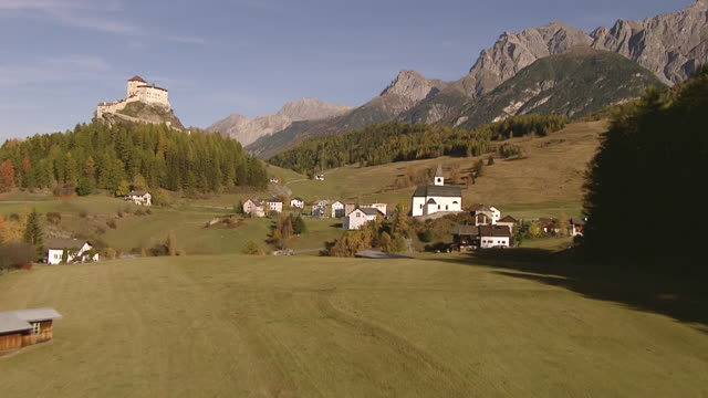 ws aerial view of village of fontana and tarasp castle with scuol / fontana, upper engadin, switzerland - 村点の映像素材/bロール