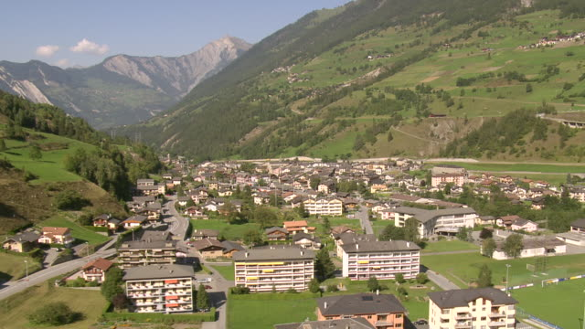 stockvideo's en b-roll-footage met ws aerial view of village with trainstation and dranse d'entremont river / orsieres, valais, switzerland - meer dan 40 seconden