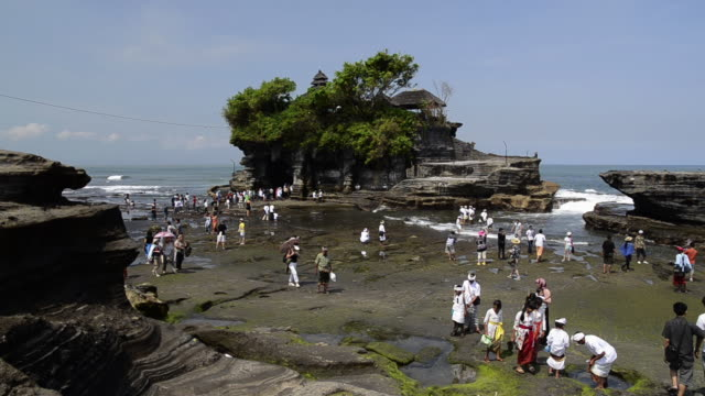 stockvideo's en b-roll-footage met ms view of visitors and pilgrims at tanah lot temple on rocky island / tanah lot, bali, indonesia - bali