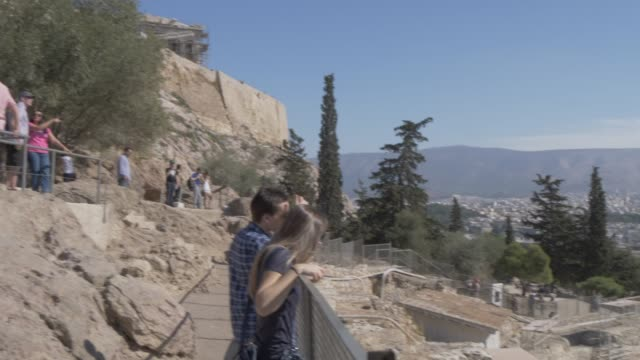 view of visitors overlooking the odeon of herodes atticus, the acropolis, athens, greece, europe - amphitheater stock-videos und b-roll-filmmaterial