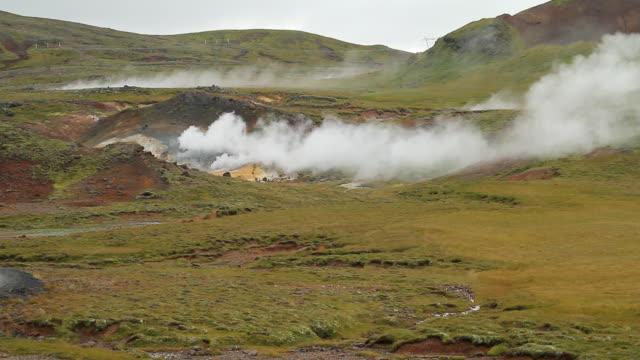 ws view of volcanic hotspots burning in grassy field / porvaldseyri, sudhurland, iceland - 噴気孔点の映像素材/bロール