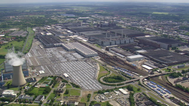 ws aerial view of volkswagen factory car parking area and cooling tower at wolfsburg with houses / germany - wolfsburg lower saxony stock videos and b-roll footage