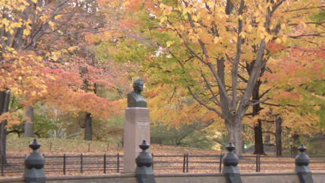 ws zi view of von schiller statue in park fall  / new york, new york,united states - figura maschile video stock e b–roll