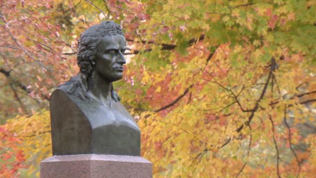 ws zo view of von schiller statue in park fall  / new york, new york,united states - figura maschile video stock e b–roll