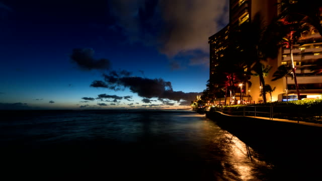 view of waikiki beach alongside the resort at night - oahu stock videos and b-roll footage