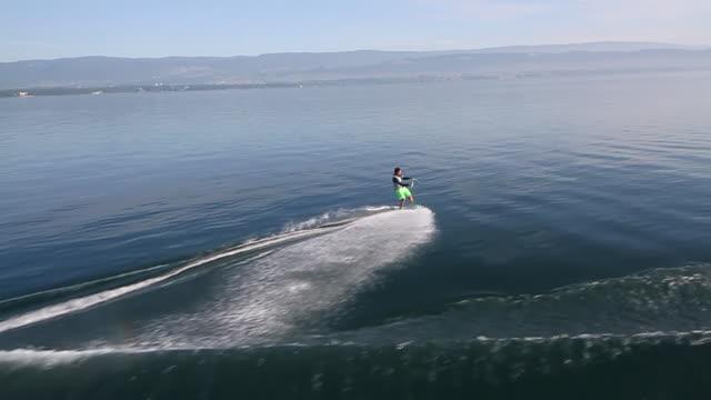 ws aerial slo mo ts view of wakeboard trick, 180â° spin with grav / geneva, switzerland  - ウェイクボーディング点の映像素材/bロール