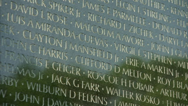 cu pan view of wall showing engraved names and reflection of visitors can be seen / washington, district of columbia, united states - vietnam veterans memorial video stock e b–roll